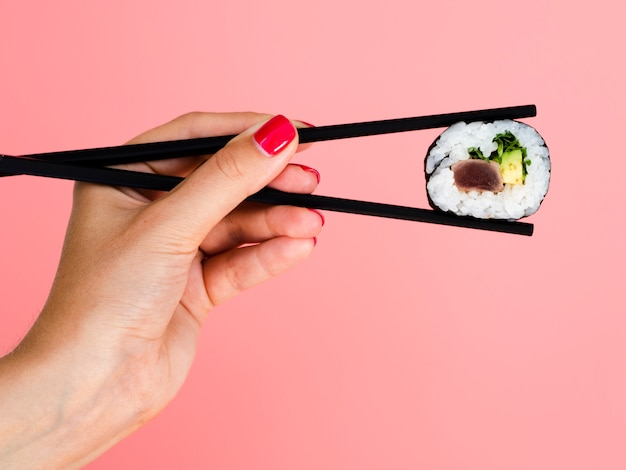 Woman holding in chopsticks a sushi roll on a rose background