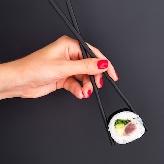 Woman holding in chopsticks a sushi roll