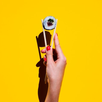 Woman holding chopsticks with sushi roll on yellow background
