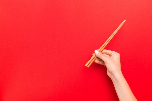 Женщина держит палочки для еды