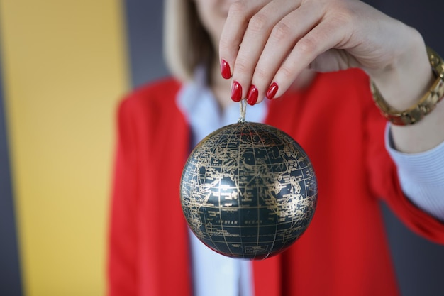 Woman holding christmas ball with world map closeup sale of roundtheworld tours concept