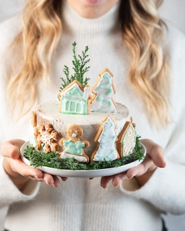 Woman holding christmas cake with gingerbread cookies, selective focus image