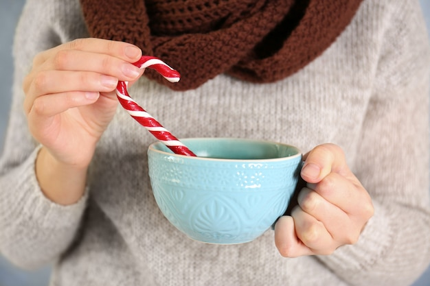 Woman holding christmas candy cane and cup in hands