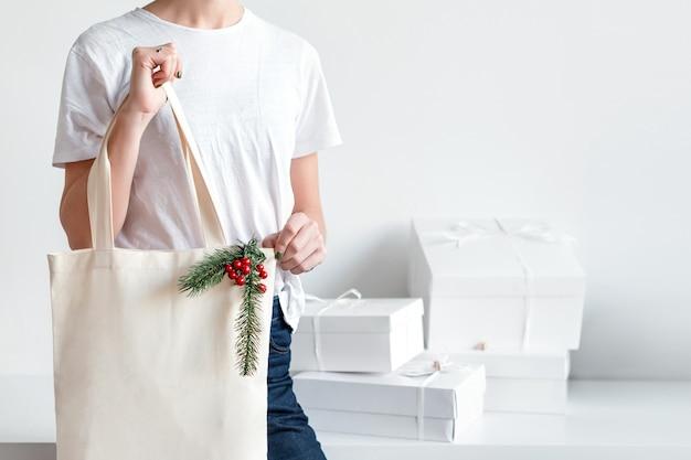Женщина, держащая рождественский мешок ткани.