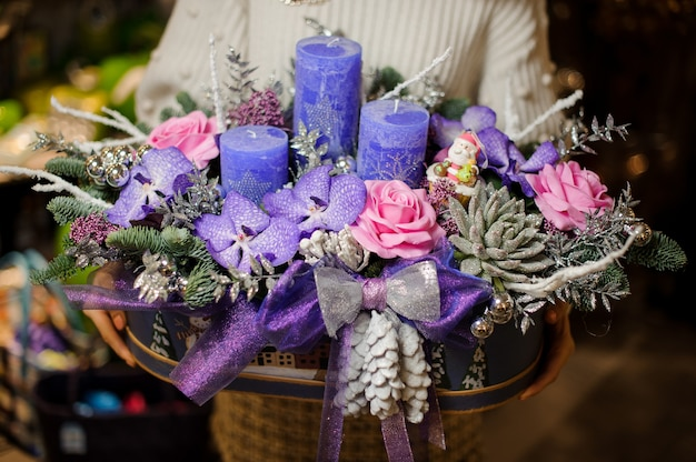 Woman holding a christmas composition with purple and pink flowers, succulents, fir-tree branches and candles in the box