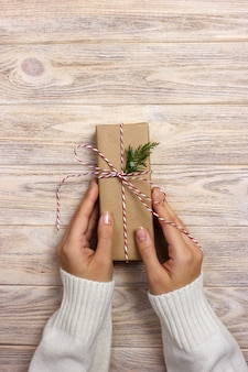 Woman holding a christmas gift in hand on wooden background.