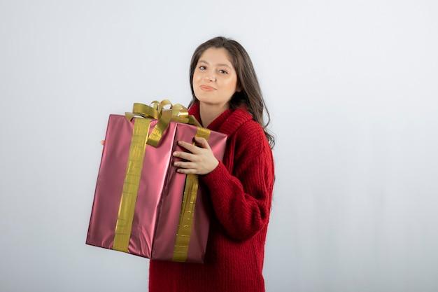 크리스마스 또는 새해 장식된 선물 상자를 들고 있는 여자.