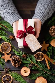 クリスマスプレゼントを持っている女性は、木製のテーブルの背景に置かれました。