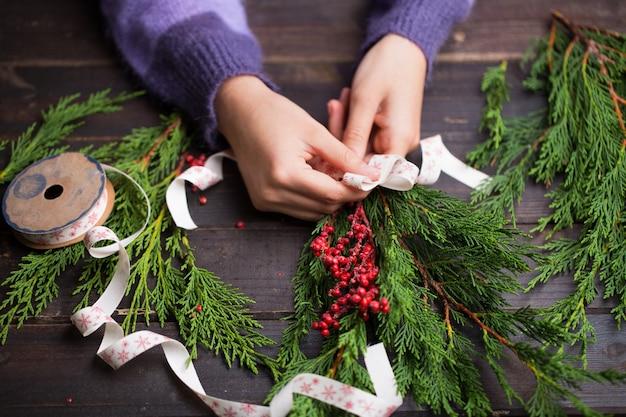 Женщина, держащая рождественские подарки на фоне деревянного стола.