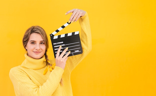 Woman holding clapboard with copy-space
