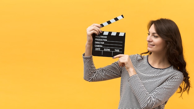 Woman holding a clapperboard next to her