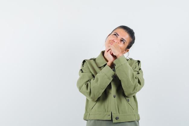 Женщина, держащая сцепленные руки во рту в куртке, футболке и мечтательная