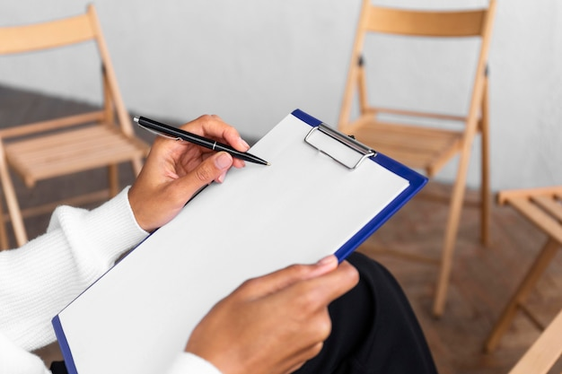 Woman holding clipboard at a group therapy session with empty chairs