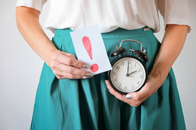 Woman holding clock at belly. missed period, unwanted pregnancy and delay in menstruation.