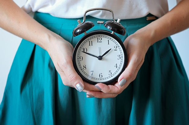 Woman holding clock at belly. missed period, unwanted pregnancy, woman's health and delay in menstruation.