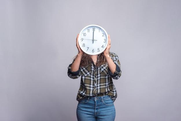 Woman holding clock on hear head on white.