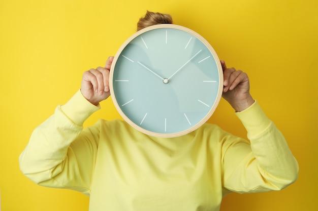 노란색 배경, 전면보기에 시계를 들고 여자