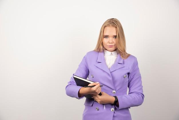 白で閉じたクリップボードを保持している女性。