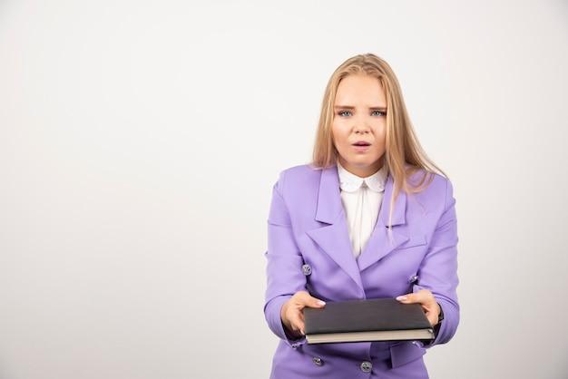 白で閉じたタブレットを保持している女性。