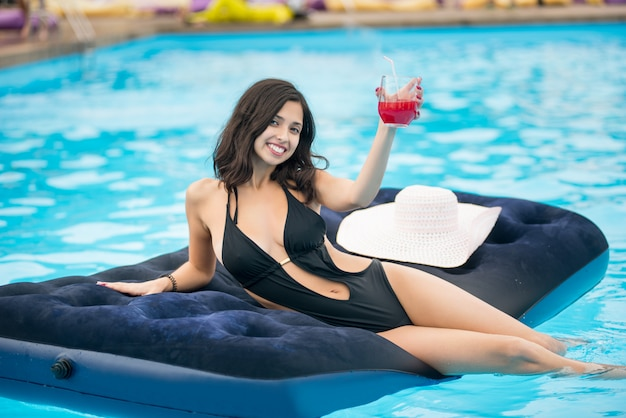 Woman holding cocktail sitting on mattress in swimming pool