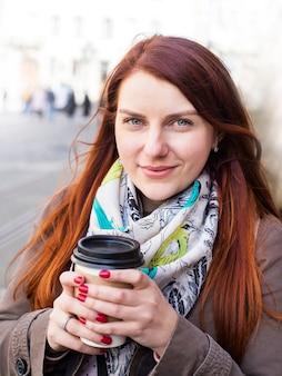 Женщина, держащая кофейную чашку и улыбку на размытой улице. солнечный весенний полдень.