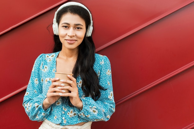 Woman holding a coffee and having headphones