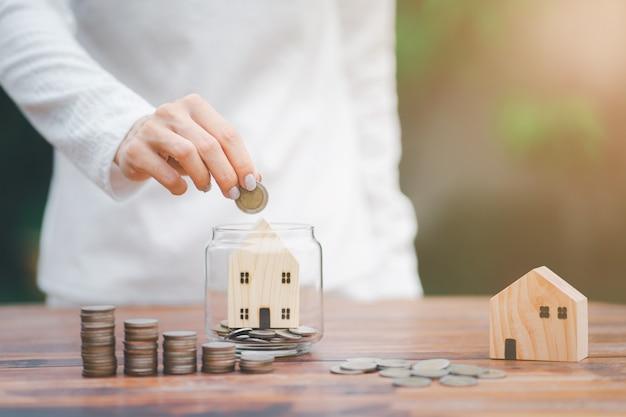 Женщина, держащая монеты, кладет в стакан. концепция экономии денег на строительство дома в будущем.