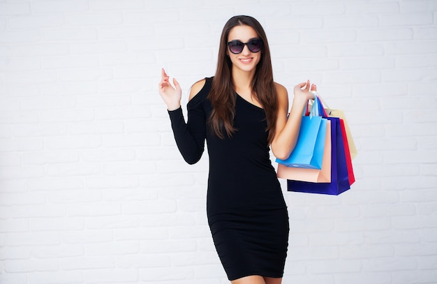 Woman holding colored bags on ligth wall