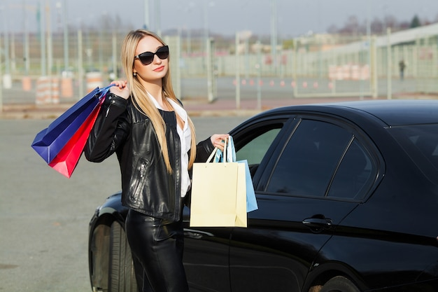 Woman holding colored bags near her car in black friday holiday
