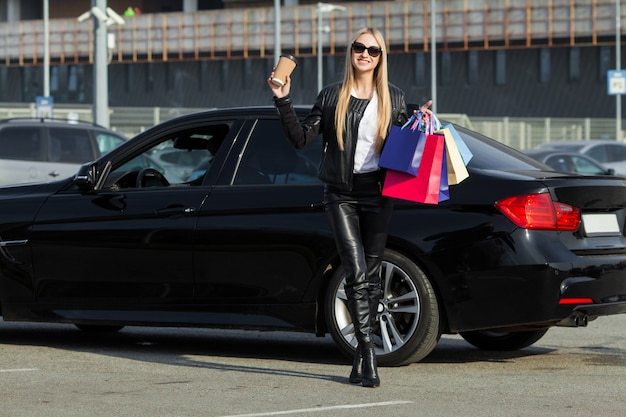 Woman holding colored bags near her car in black friday holiday.