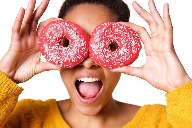 Woman holding colorful donuts against her eyes