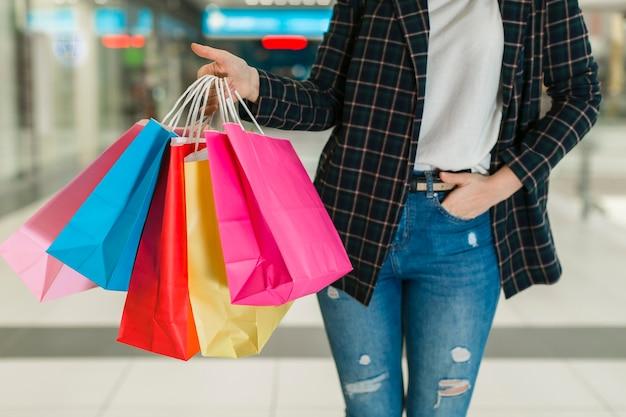 Donna che tiene i sacchetti della spesa variopinti