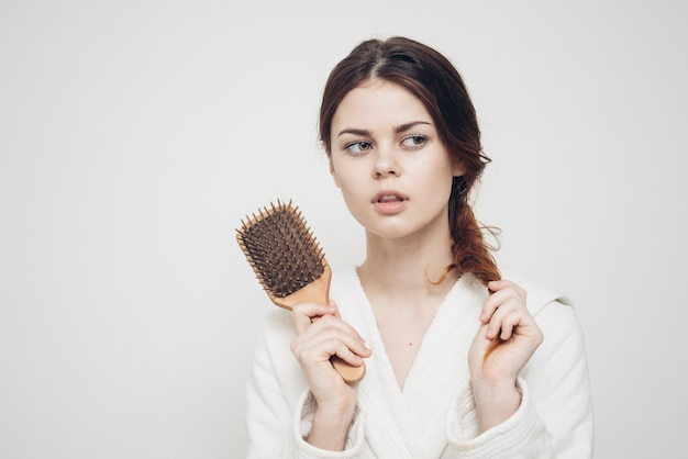Woman holding a comb in her hand and tangled hair fragility health problems.