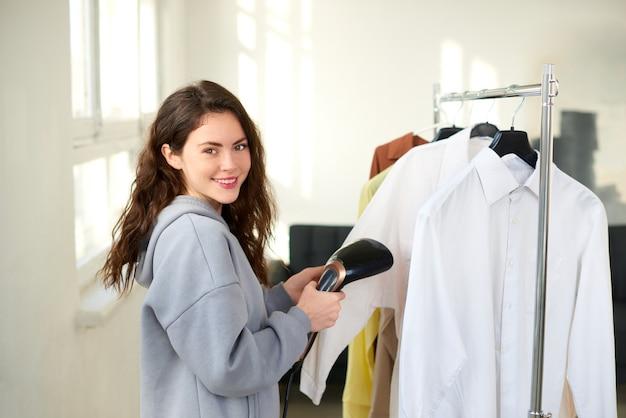 Женщина, держащая компактный ручной отпариватель и стирающая белую рубашку дома