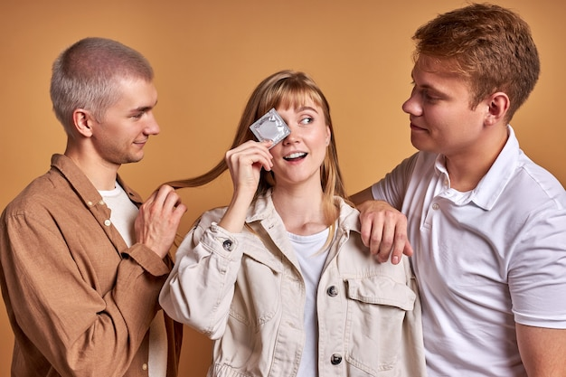 Woman holding condom in hands, with two men isolated in studio