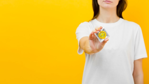 Woman holding a condom with copy space