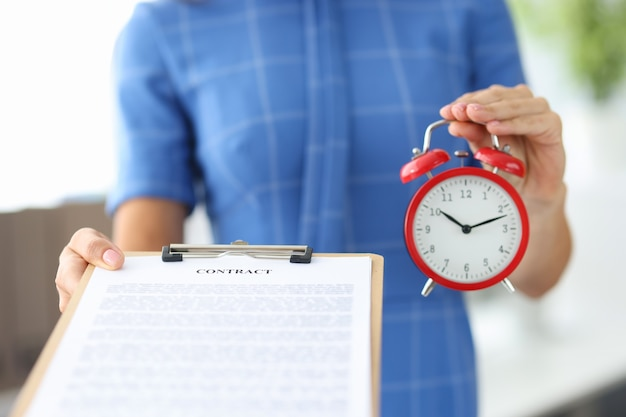 Woman holding contract and red alarm clock in her hands closeup schedule of working hours