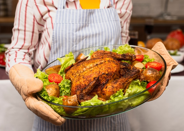 Woman holding the cooked turkey close-up