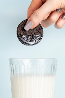 Woman holding a cookie above glass of fresh milk