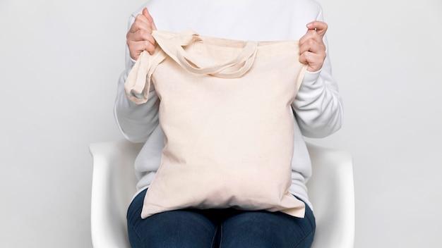Donna che tiene una borsa di tote del tessuto dello spazio della copia