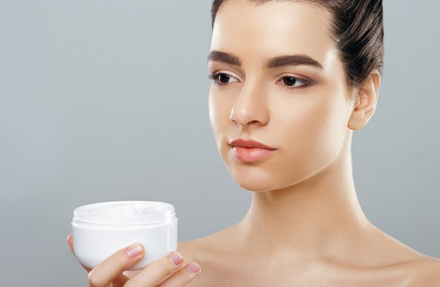 Woman holding cosmetic cream. beauty face.  girl with clean fresh skin. closeup.