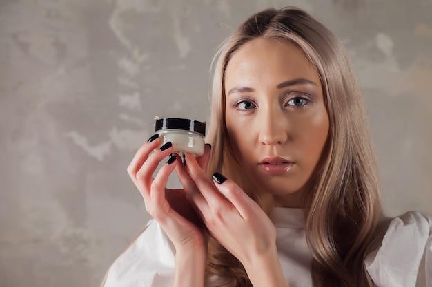 顔の肌に塗る化粧クリームを持っている女性。女性は葉から日陰で古い壁の背景にクリームを保持します。健康的なライフスタイルとセルフケアの広告コンセプト。 spaのコピースペース