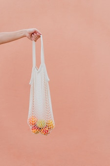 Woman holding cotton bag with fruit.