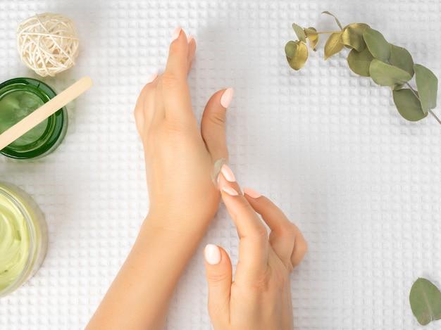手にクリームを保持している女性。白いタオルの背景に美しい女性の手。手が気になります。きれいな肌。爪に淡いピンクのマニキュアと美しい女性の手のクローズアップ画像。