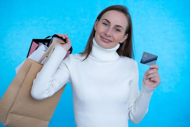 파란색 벽에 신용 카드와 쇼핑백을 들고 여자.