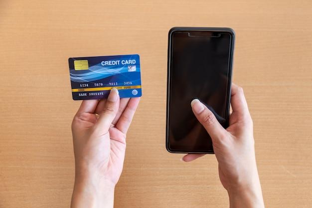 クレジットカードとスマートフォンを保持している女性。スマートフォンを使ったインターネットでのオンラインショッピング