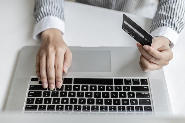 Женщина, держащая кредитную карту и набирающая текст на клавиатуре ноутбука, заполняет данные кредитной карты, чтобы оплатить заказ на сайте покупок в интернете. интернет-магазины и концепция оплаты кредитной картой