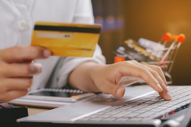 Женщина, держащая кредитную карту и использующая портативный компьютер. интернет-магазины, электронная коммерция, интернет-банкинг