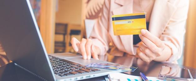 신용 카드를 들고 온라인 쇼핑을 하는 노트북을 사용하는 여자. 웹 배너용. 프리미엄 사진