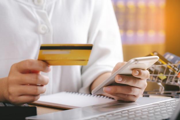クレジットカードを持ってスマートフォンを使用している女性。オンラインショッピング、eコマース、インターネットバンキング